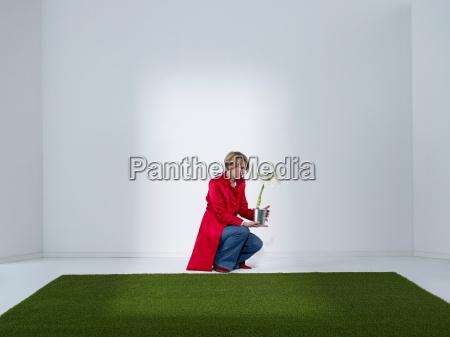 women looking at flower in green