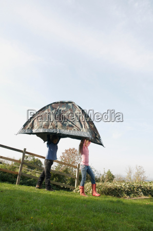 boy and girl carrying tent
