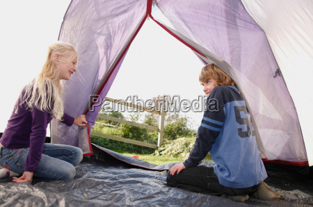 boy and girl sitting in tent