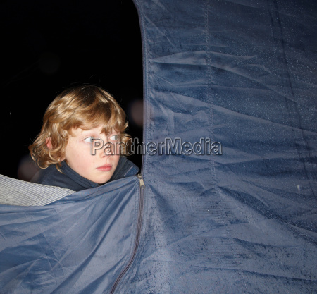 boy looking out of tent at