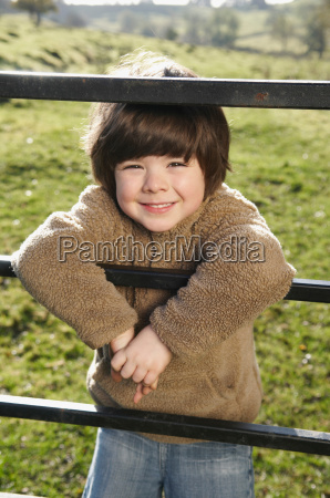 young boy on gate in countryside