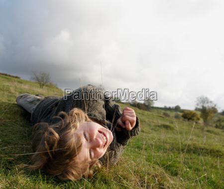 boy lying on grass on hillside