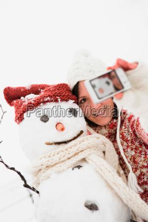 woman taking photo of snowman