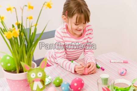 girl painting eggs for easter