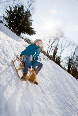 girl riding a sledge in snow