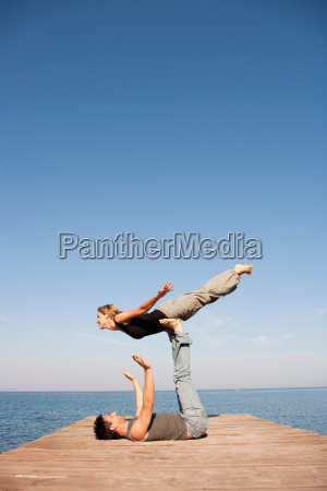 couple playing air plain on pier