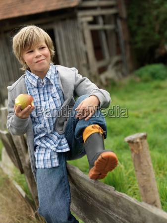 boy eating apple sitting on fence