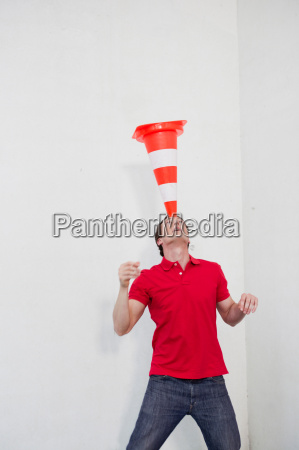 man balancing a pylon on his