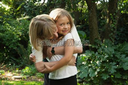 pregnant mother hugging daughter