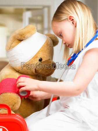 girl playing doctor with teddy bear