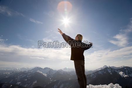 man raising hands toward sky