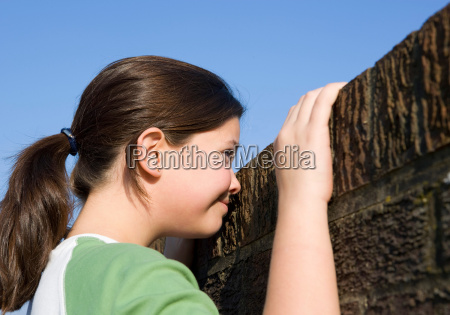 girl looking over wall