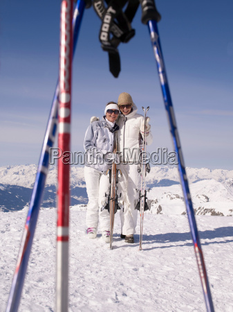 two women with skis smiling at