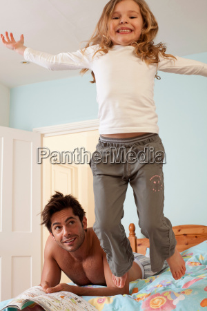 girl jumping off bed by father