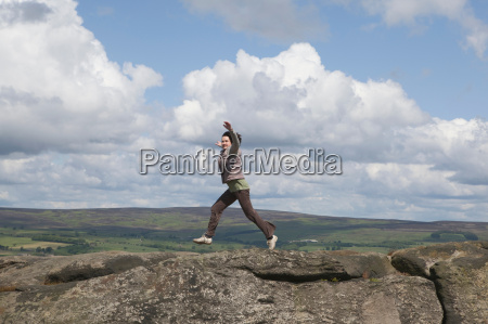 woman jumping on rock