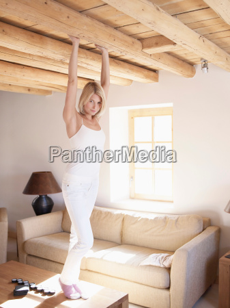 woman standing on table in living