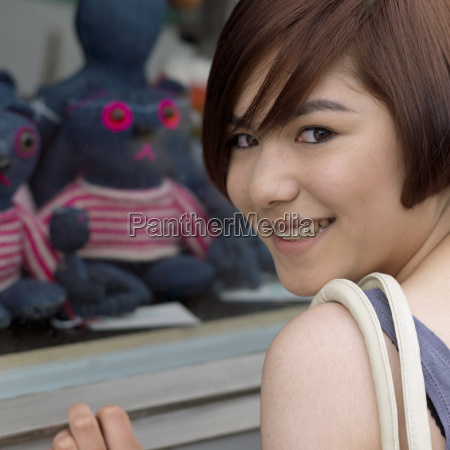 young woman at shop window smiling