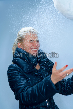young woman with snowball and snow