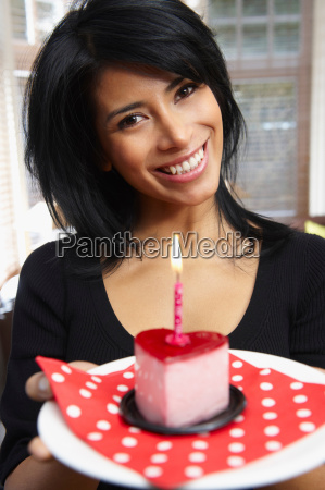 woman holding a heart shaped cake