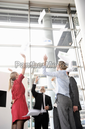 business team throwing papers in the