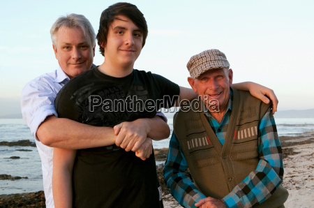 three generations of men on beach