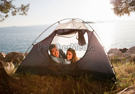 couple lying in tent by sea
