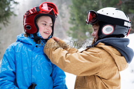 young boy helping girl do up