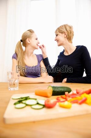 young women preparing food eating