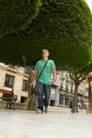 man walking through city park