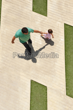 father walking with infant daughter