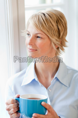young woman at home holding cup