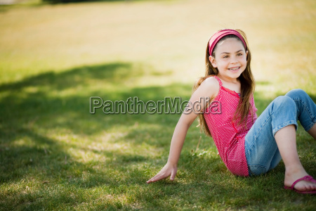 young girl sitting on grass laughing