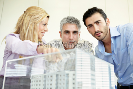 3 people looking at architectural model