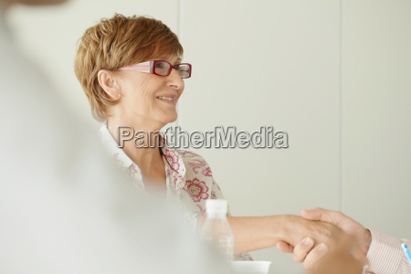 older business woman shaking hands