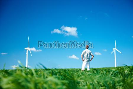 man in field looking at wind