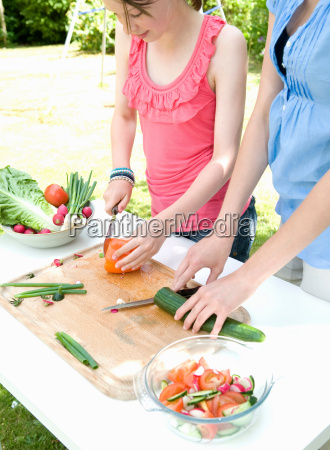 mother and daughter prepare salad in