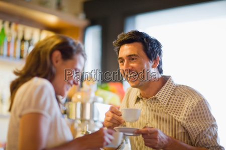 man with coffee and woman smiling