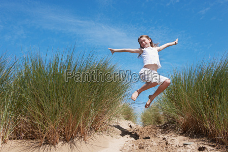 young girl jumping in sand dunes