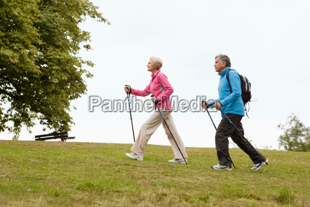 mature couple nordic walking in park