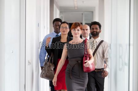 business people walking down corridor