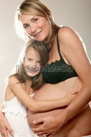 pregnant woman with daughter smiling