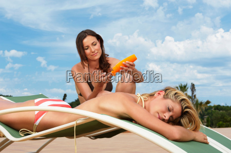 woman on sun lounger applying sunblock