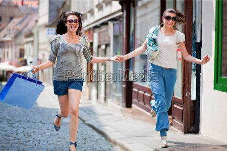 young women running along street