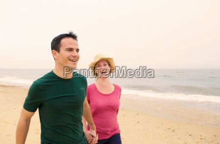 happy couple walk on beach
