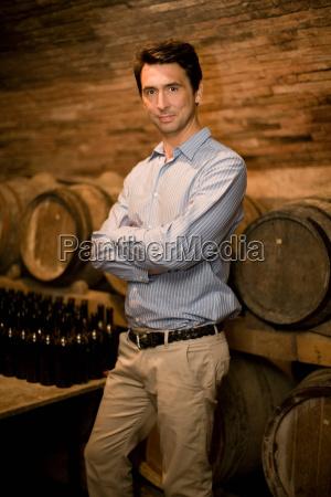 man standing in wine cellar