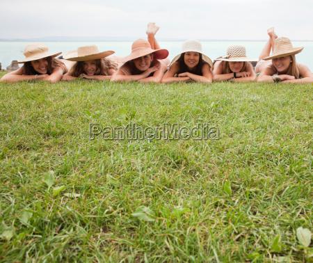 women in straw hats lie on