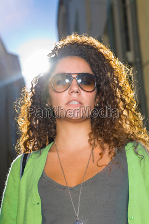 young woman wears sunglasses in street