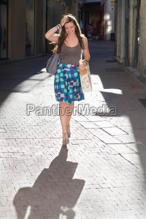 young woman walks in street with