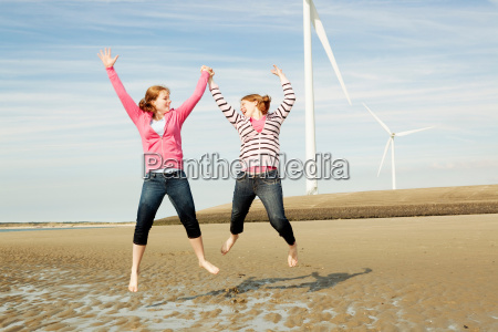 two girls jumping on beach with