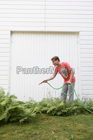young man watering his plants
